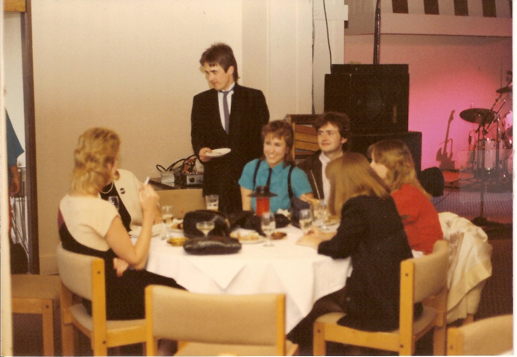 Dinner party at venue before Eagertones show, with Michael Adams, guitarist standing, and Sean Onnery, bassist sitting, with assorted hanger ons.